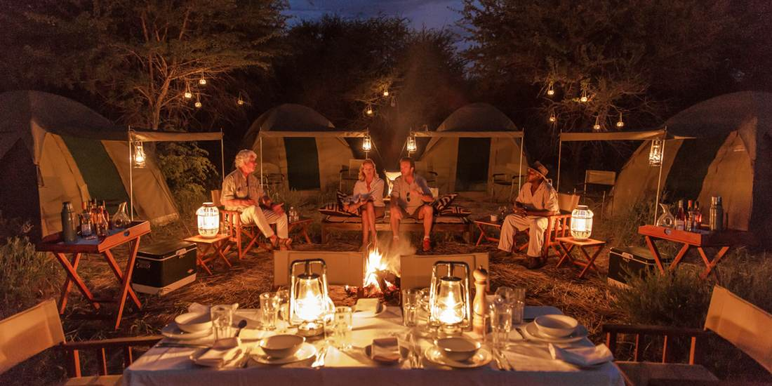 Sharing safari stories around the campfire on a Kalahari fly-camp
