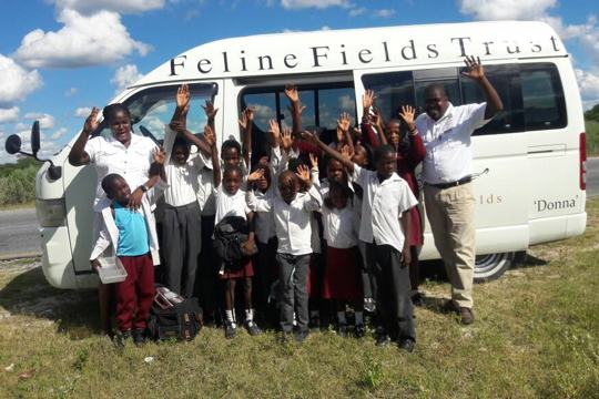 Kids waving before embarking on the Feline Feields Trust bus